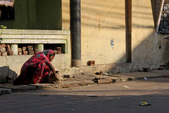 Poor Indian woman sit on a ruined street Royalty Free Stock Image