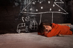 Poor kid on the street thinking of Christmas gifts Stock Images
