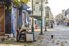 A poor man on a wheelchair, walks through the streets of Bourgas / Bulgaria / 10.18.2016 / and dug in the street bin. Poor lifestyle of people with disabilities royalty free stock photos