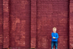 Poor little child near big wall. Depressed abused poor little child (boy, kid) sitting near big red brick wall Stock Photography