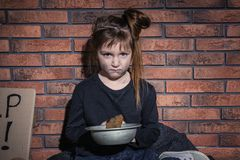 Poor little girl with bread against wall. Poor little girl with bread against brick wall royalty free stock photography