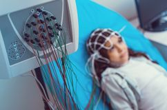 Poor little girl getting her brain analyzed at laboratory. Serious diagnostics. Selective focus on an electroencephalography machine with nodes analyzing brain royalty free stock photos