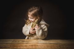 Poor little girl hugs a teddy bear straw Royalty Free Stock Images