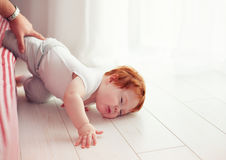 Poor little toddler baby fell down from the bed while crawling on it. Dad missed to catch him Stock Photography