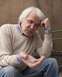 Poor lonely male pensioner. Sitting on an iron bed, on which, instead of a mattress, wire mesh stock photography