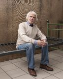 Poor lonely male pensioner. Sitting on an iron bed, on which, instead of a mattress, wire mesh stock photo