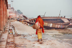Poor lonely man walking past famous Ganges river with rustic riverboats. VARANASI, INDIA - JAN 1: Poor lonely man walking past famous Ganges river with rustic stock photo