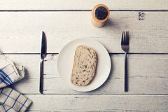 Poor lunch - slice of bread on a plate and cutlery. On wooden table Royalty Free Stock Photography