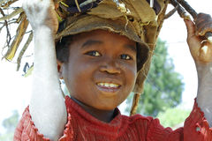 Poor malagasy boy carrying branches on his head Royalty Free Stock Photography