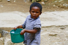Poor malagasy boy carrying plastic water bucket. Poverty Royalty Free Stock Image