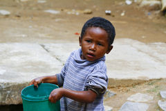 Poor malagasy boy carrying plastic water bucket. Poverty Stock Photo