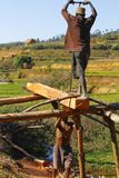 Poor malagasy men cutting timber Stock Photo