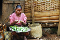 Poor Malagasy woman preparing food in front of cabin. Madagascar royalty free stock image