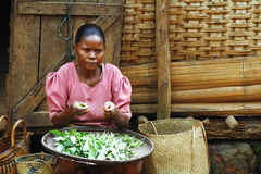 Poor Malagasy woman preparing food in front of cabin Royalty Free Stock Photos