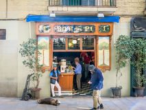 Poor man and bar. Poor disabled man passing a bar in Barcelona, Spain royalty free stock image