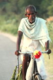 Poor man on a bicycle. Going to work early in the morning stock image