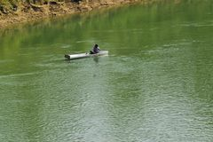 A poor man boating and fishing under the river. Village poor man boating under river fishing putting royalty free stock photography
