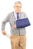 Poor man with broken arm showing his empty pocket. Isolated on white background royalty free stock photography