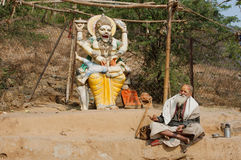 Poor man in clothes of Indian pilgrim resting by the sculpture of the hindu god Narasimha Stock Images