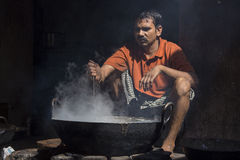 Poor man cooks in old wok the fire, India Stock Photo