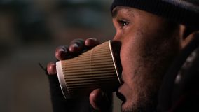 Poor man drinking from paper cup with tears on face, eyes shining with hope stock video