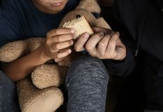 Poor man giving piece of bread to his son. Focus on hands stock photos