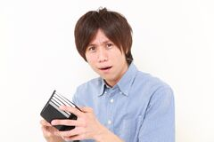 Poor man lokking for his empty wallet. Studio shot of young Japanese man on white background royalty free stock photo