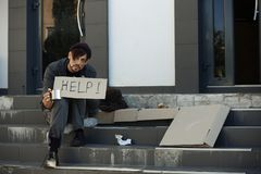 Poor man with mug begging and asking for help. On city street royalty free stock photos