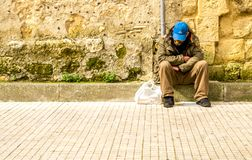 Homeless Man. A poor man sat on a kerb stone with no money to eat and nowhere to go royalty free stock photography