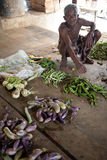 Poor man selling vegetables. On a market-place Royalty Free Stock Image