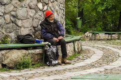 Poor man sitting on bench. Poor man looking sideways and resting after finishing his meal on April 13, 2014 in Bucharest, Romania Stock Photo