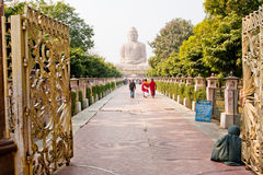 Poor man waiting for tourists near Buddha statue Stock Photos