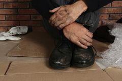 Poor man wearing old dirty shoes sitting. On floor stock images