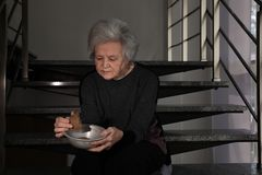 Poor mature woman with bowl and bread on stairs. Space for text stock images