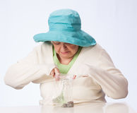 Poor Mature Woman Looks in Bag at Coins. Mature Caucasian woman in turquoise hat looks in plastic bag for the coins in her possession White table and background Stock Photo