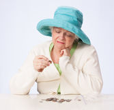 Poor Mature Woman Looks at Coin and Thinks with Hand Under Chin Stock Photo