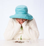 Poor Mature Woman Looks at Coins with Both Hands Cupping Chin. Mature Caucasian woman in turquoise hat looks down at a coins from plastic bag with both hands Royalty Free Stock Images
