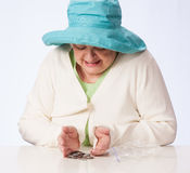 Poor Mature Woman Looks at Coins on table. Mature Caucasian woman in turquoise hat looks on table for the coins in her possession from plastic bag. White table Stock Photos