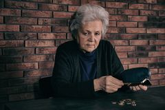 Poor mature woman pouring coins out of wallet. At table royalty free stock photo