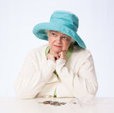 Poor Mature Woman Thinks with Hands Under Chin Royalty Free Stock Photography
