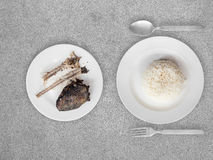 Poor meal of rice and fish bones. Royalty Free Stock Photography