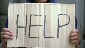 Poor mixed-raced boy holding cardboard asking for help, social problems violence