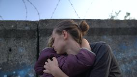 Poor mom hugging child fenced in ghetto, unemployment, lower population strata. Stock footage stock footage