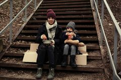 Poor mother and daughter with bread sitting on stairs. Outdoors royalty free stock photo