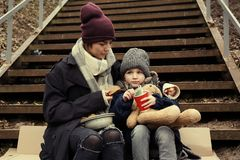 Poor mother and daughter with bread sitting on stairs. Outdoors royalty free stock images