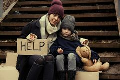 Poor mother and daughter with HELP sign sitting on stairs. Outdoors royalty free stock images