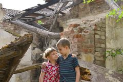 Poor and neschatnye children on the ruins of a burnt house. The brothers suffered a natural disaster. Poor and neschatnye children on the ruins of a burnt house royalty free stock photos