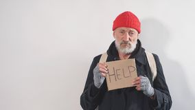 Poor old-aged bum in red hat and street wear holding cardboard sign