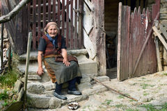 Poor old Bulgarian country woman in worn out clothes sitting on the steps in front of her ruining cottage Stock Images