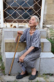 Poor old Bulgarian woman with walking cane and worn out, shabby dress sitting on stairs on the street of Varna Stock Photos